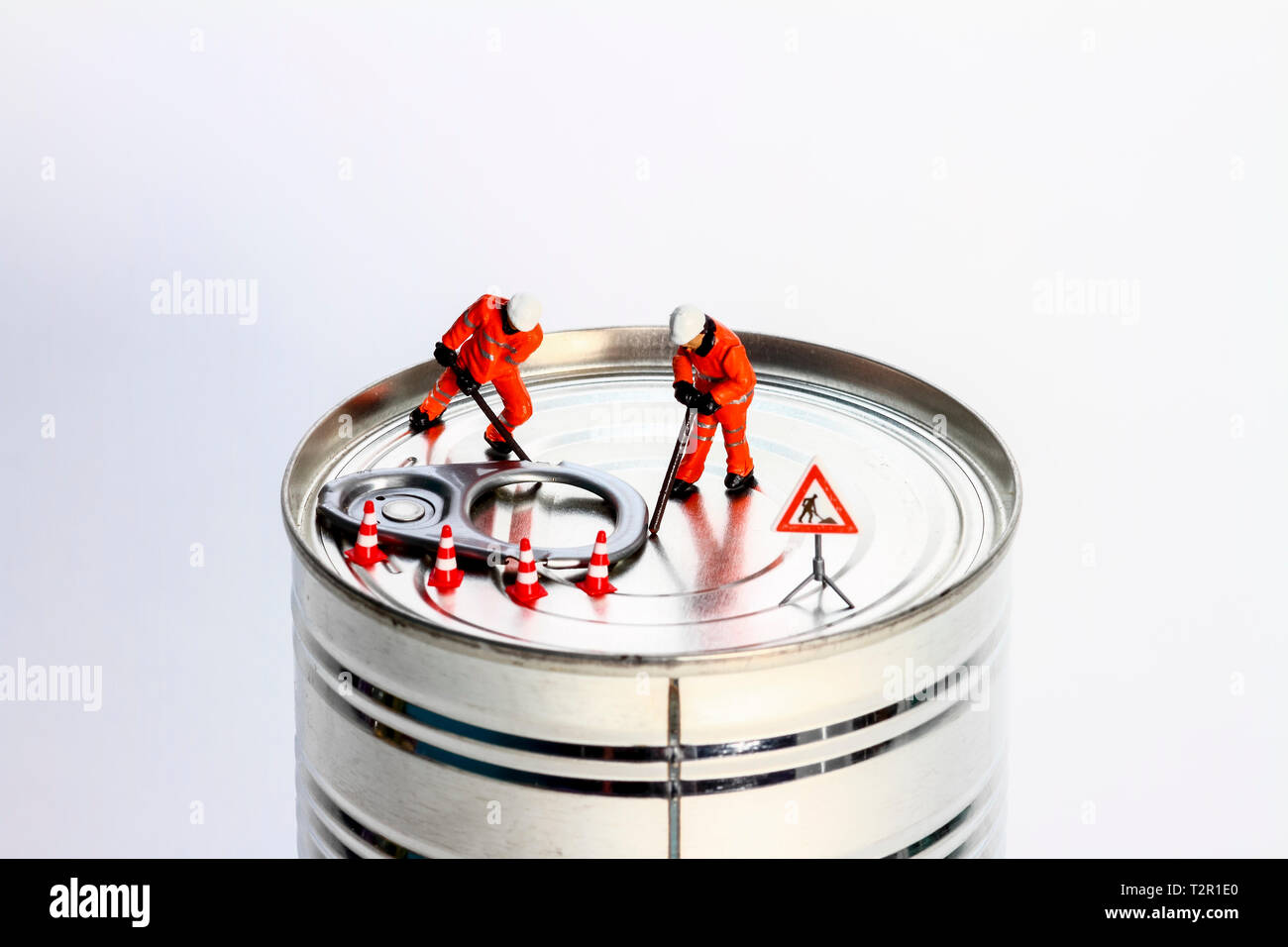 Conceptual diorama image of miniature figures trying to prise open a tin can - Stock Image