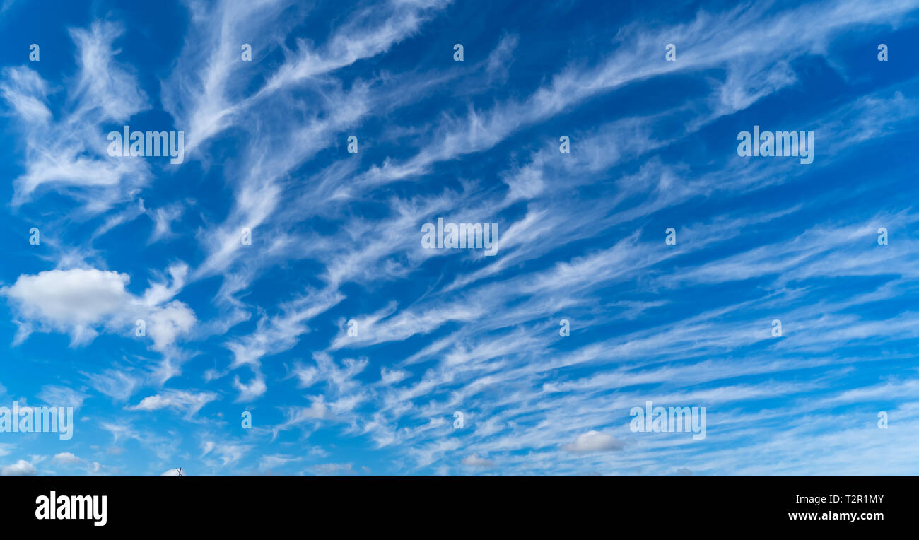 A Photo of a blue sky with white clouds forming different shapes - Stock Image