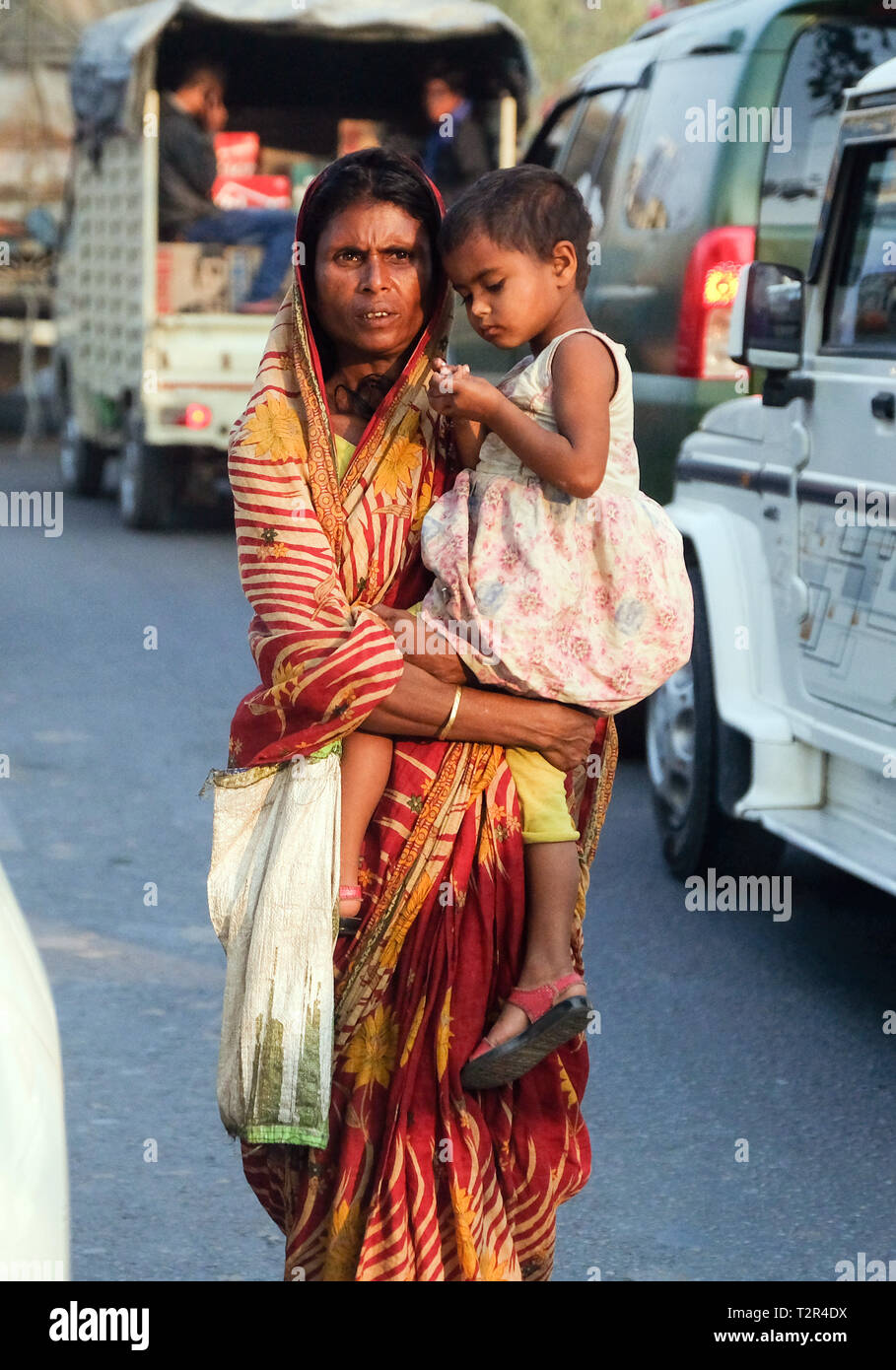 Beggar woman with her child between cars on a street in Guwahati, Assam state, India  ---   Bettlerin mit ihrem Kind zwischen Autos auf einer Straße in Guwahati, Bundesstaat Assam, Indien - Stock Image