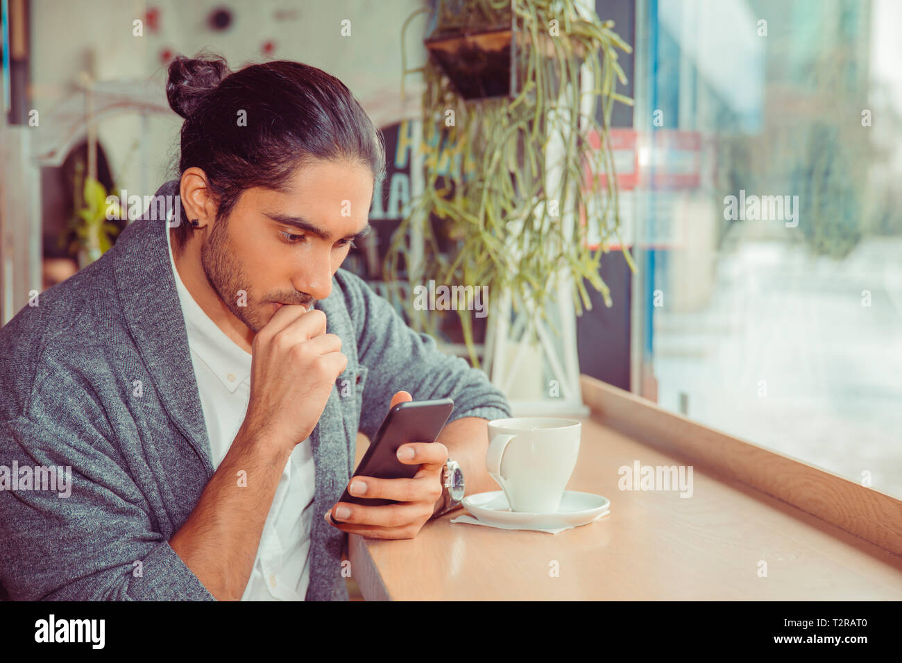 Serious man looking at phone, worried by news he received. Closeup portrait of a handsome guy wearing white shirt, gray blouse sitting near window at  Stock Photo