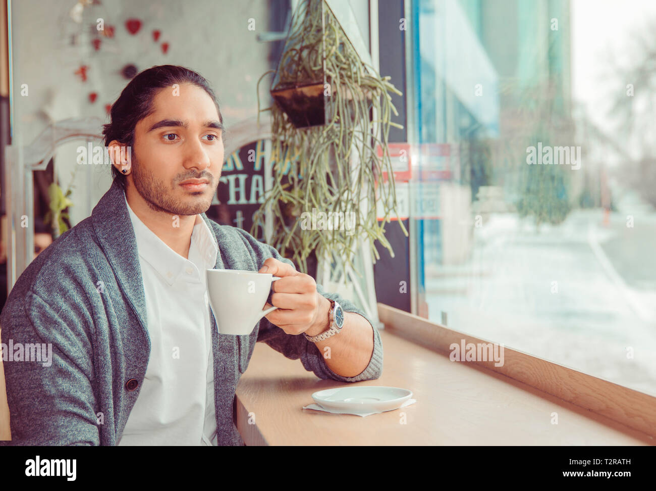 Sad thoughtful man looking down pensive holding cup. Closeup portrait of a handsome guy wearing casual clothing sitting near window at table in coffee - Stock Image