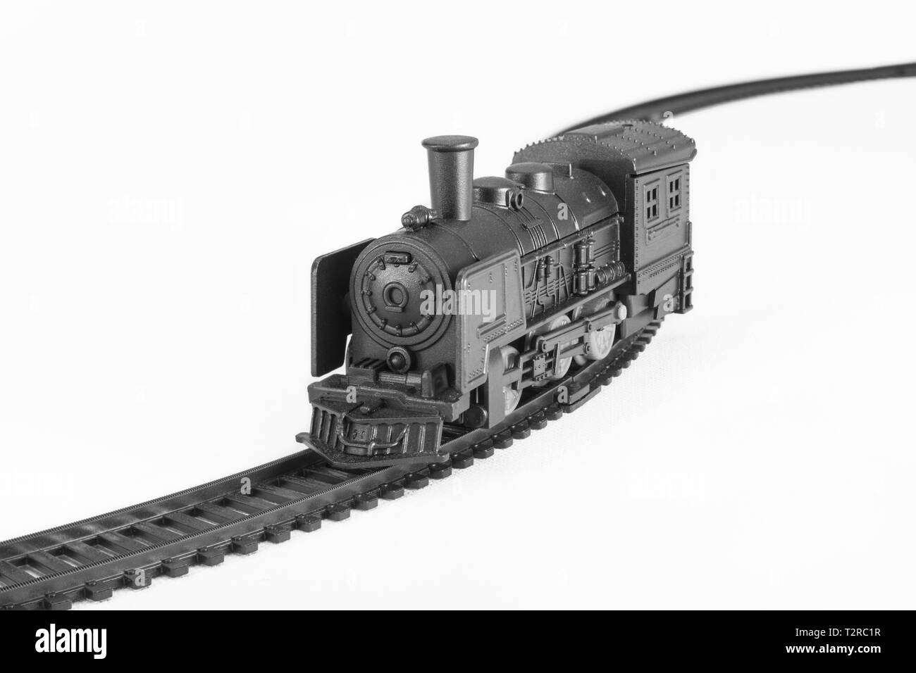Black painted toy steam engine model and track. Metaphor On the Right Track, gravy train, old railroads, rail network, toy train set, career track. Stock Photo