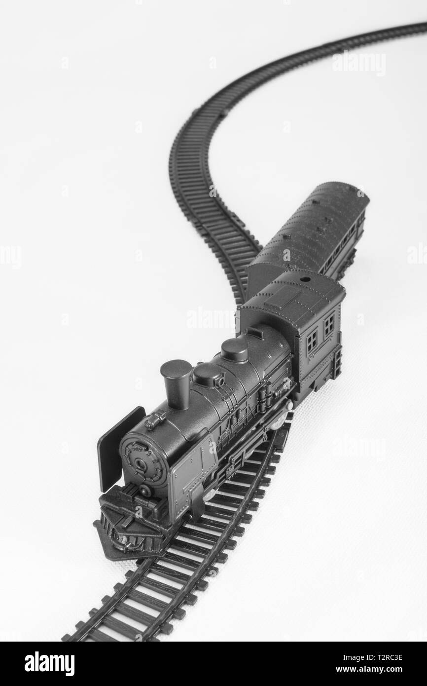 Black painted toy steam engine model. Metaphor off track, financial crash, knocked off course, train accident, end of gravy train, Oops, train wreck Stock Photo