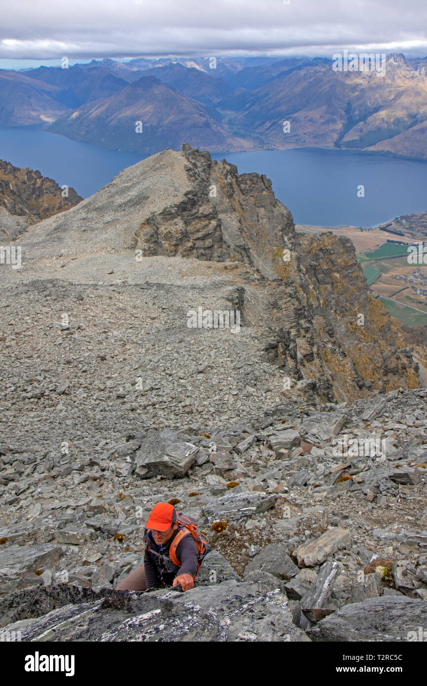 Man scrambling on the Queen's Drive on the Remarkables above Queenstown - Stock Image