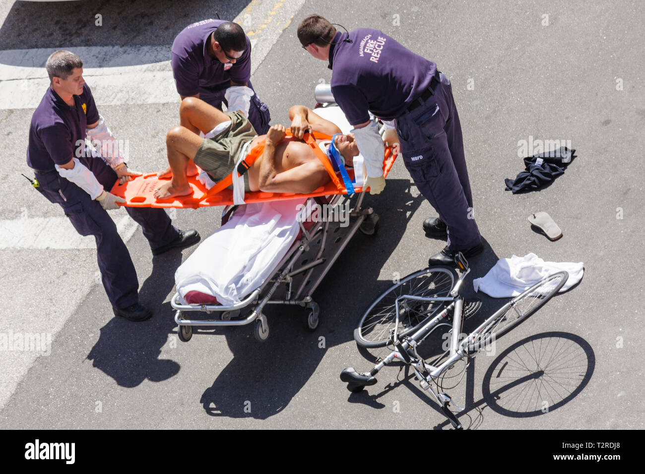 Miami Beach Florida intersection accident cyclist bicycle injury injured man fire rescue paramedic emergency medical service str Stock Photo