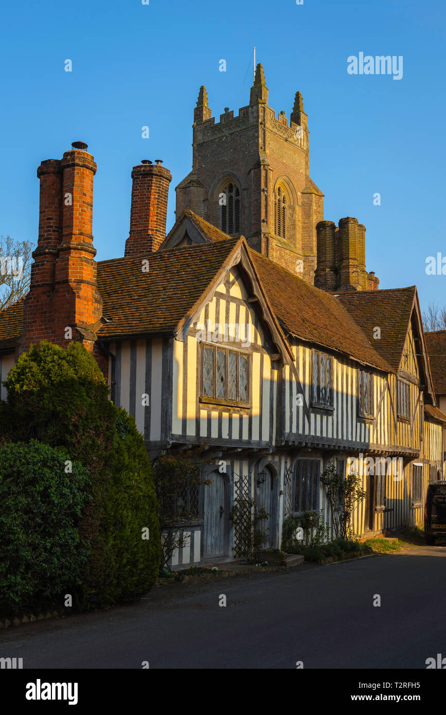 View of a row of medieval half timbered houses in the village of Stoke By Nayland with the local church tower rising behind them, Suffolk, England, UK - Stock Image