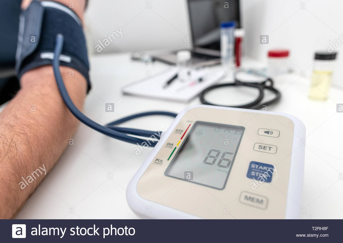 Having blood pressure read using medical device Stock Photo