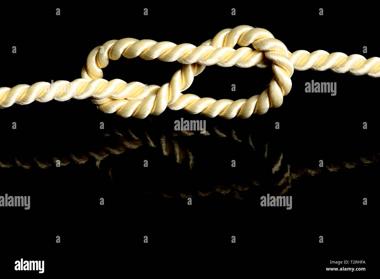 A knot against a black background. The node is reflected on the background. - Stock Image