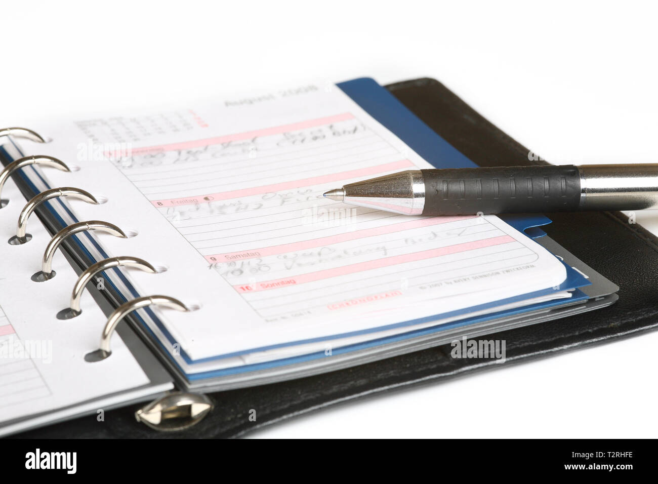 An open pocket calendar with a pen on it. Isolated against a white background. - Stock Image