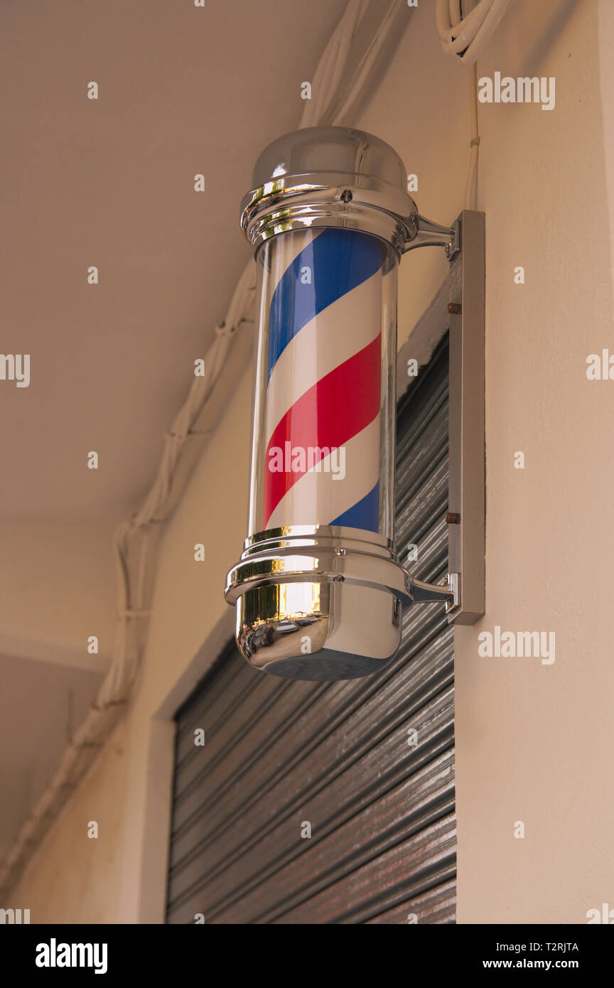 Barber's pole of white and red colors, anchored to the wall of the barbershop or village barbershop - Stock Image