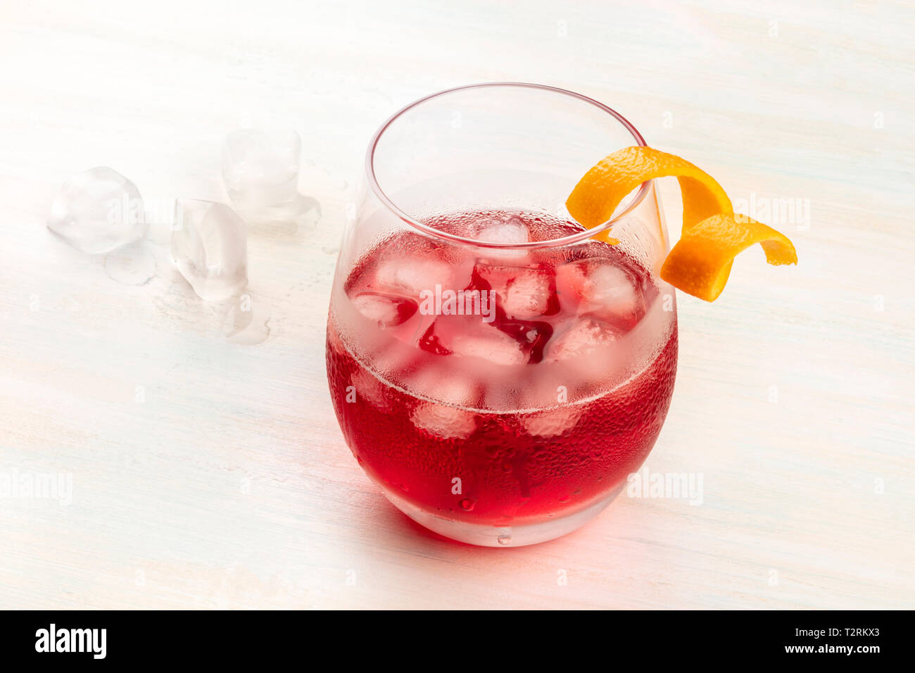 A vibrant Negroni cocktail with campari and an orange zest twist, with ice cubes on a white wooden background, with copy space Stock Photo