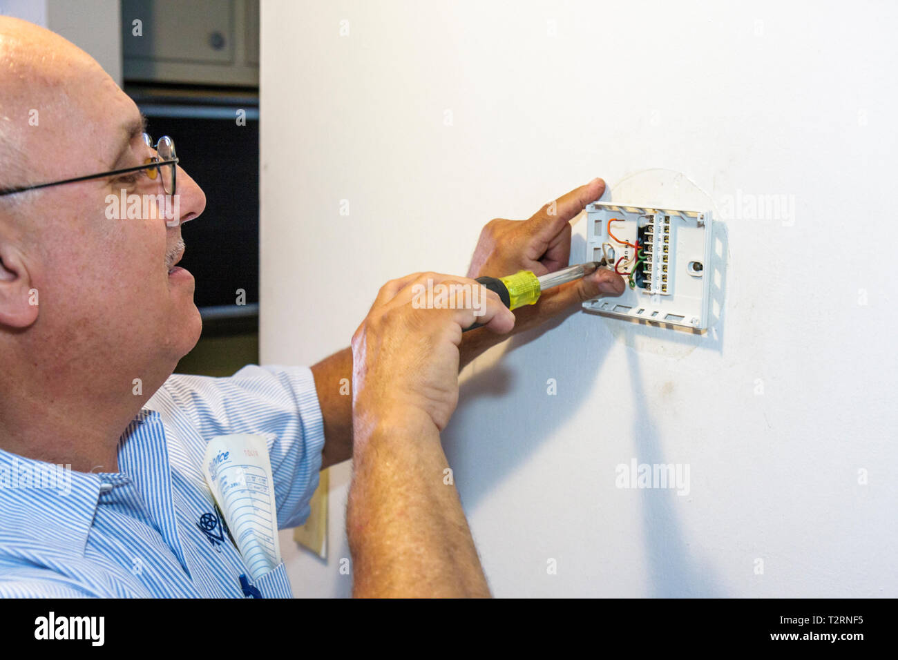 Miami Beach Florida Presidential Condominiums air conditioning mechanic Hispanic man worker repairman digital thermostat install - Stock Image