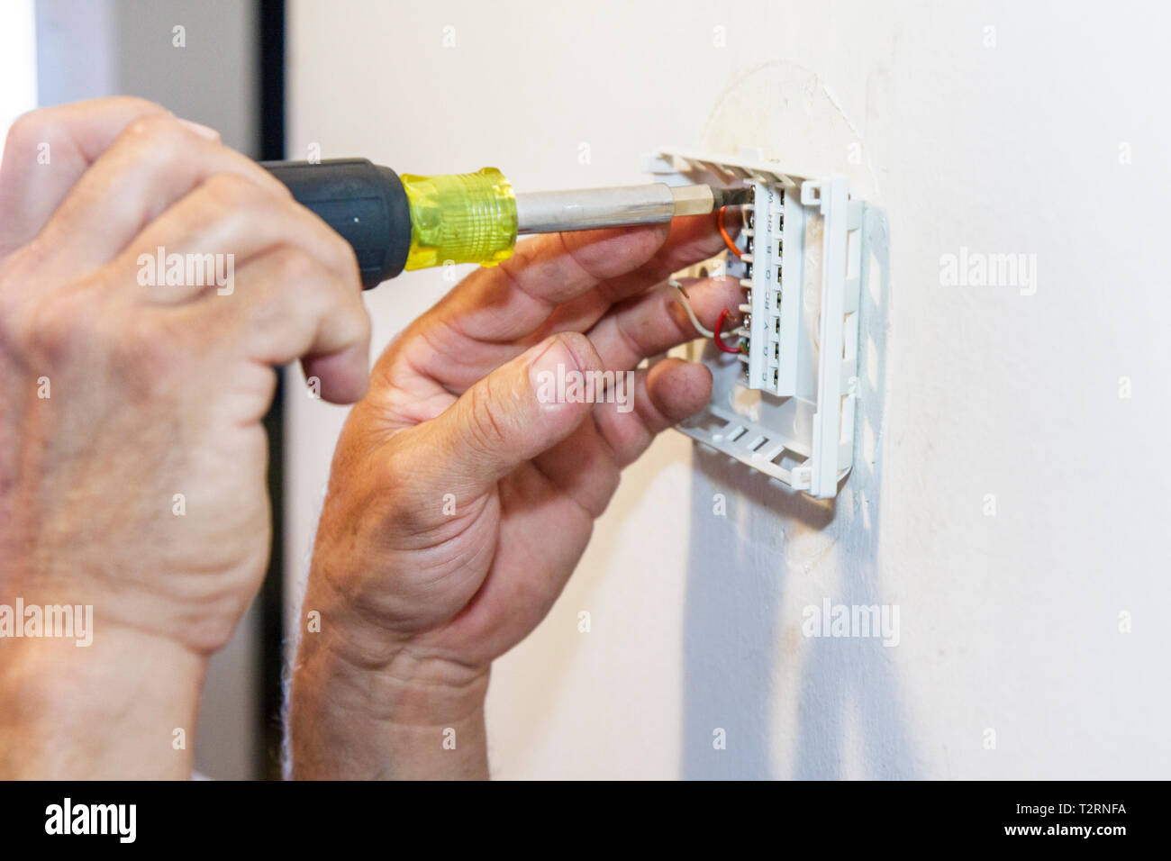 Miami Beach Florida Presidential Condominiums air conditioning mechanic hands worker repairman digital thermostat install instal - Stock Image