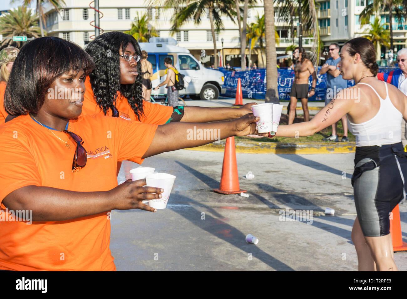 Miami Beach Florida Lummus Park Nautica South Beach Triathlon competitors sport fitness water station hydrate Black woman women - Stock Image