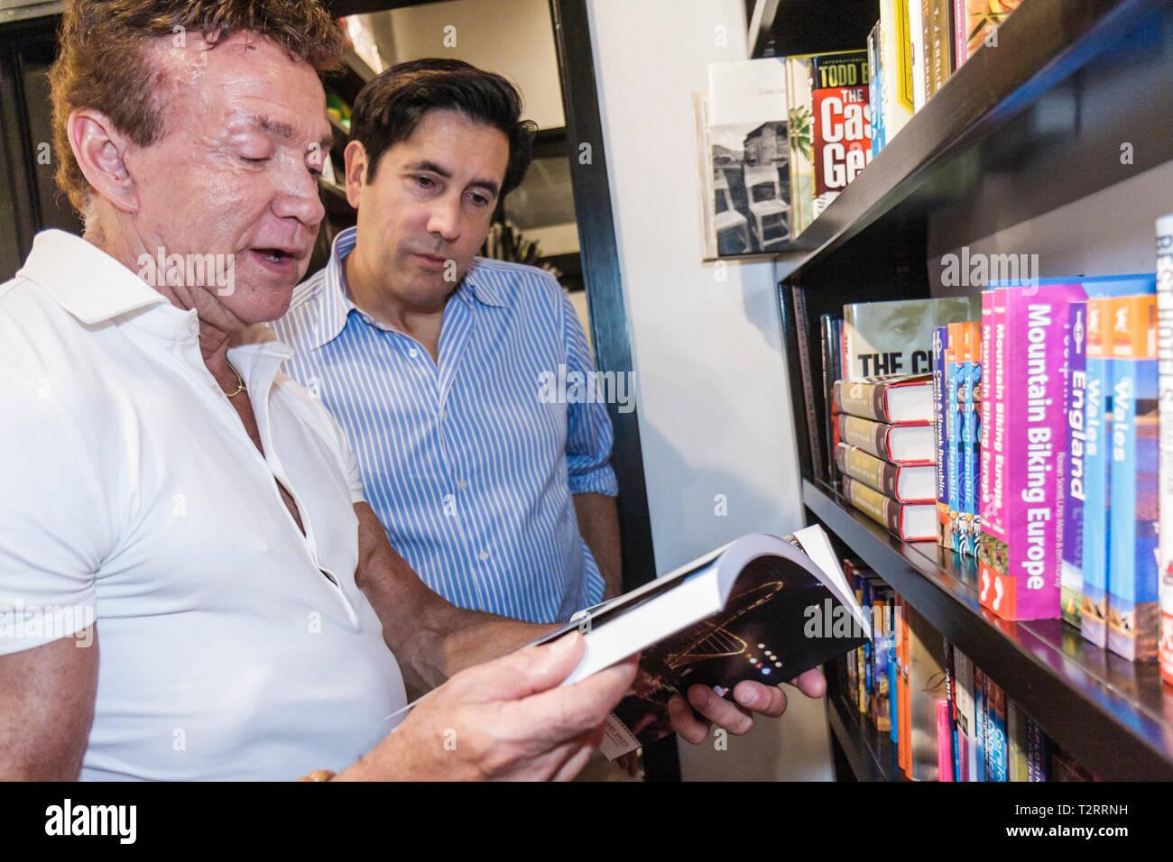 Miami Beach Florida Lincoln Road pedestrian mall shopping Gay Pride Event Books and Books man men shelves travel shopping readin - Stock Image