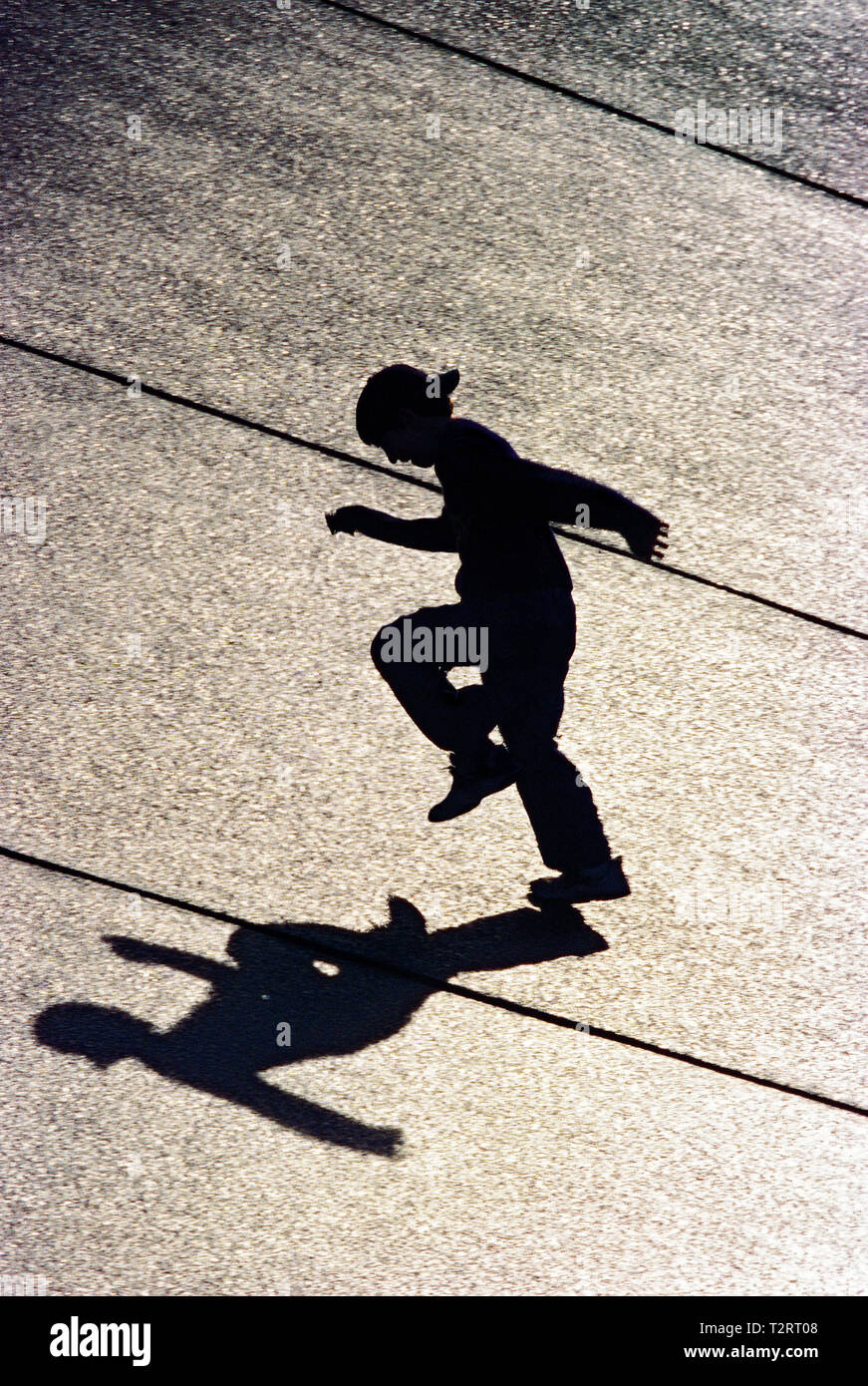 Silhouette  of a boy running on a concrete fountain downtown Seattle - Stock Image