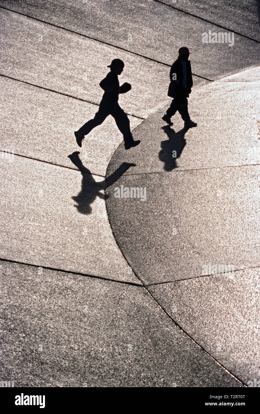 Sillhouette  of two boys running on a concrete fountain downtown Seattle - Stock Image