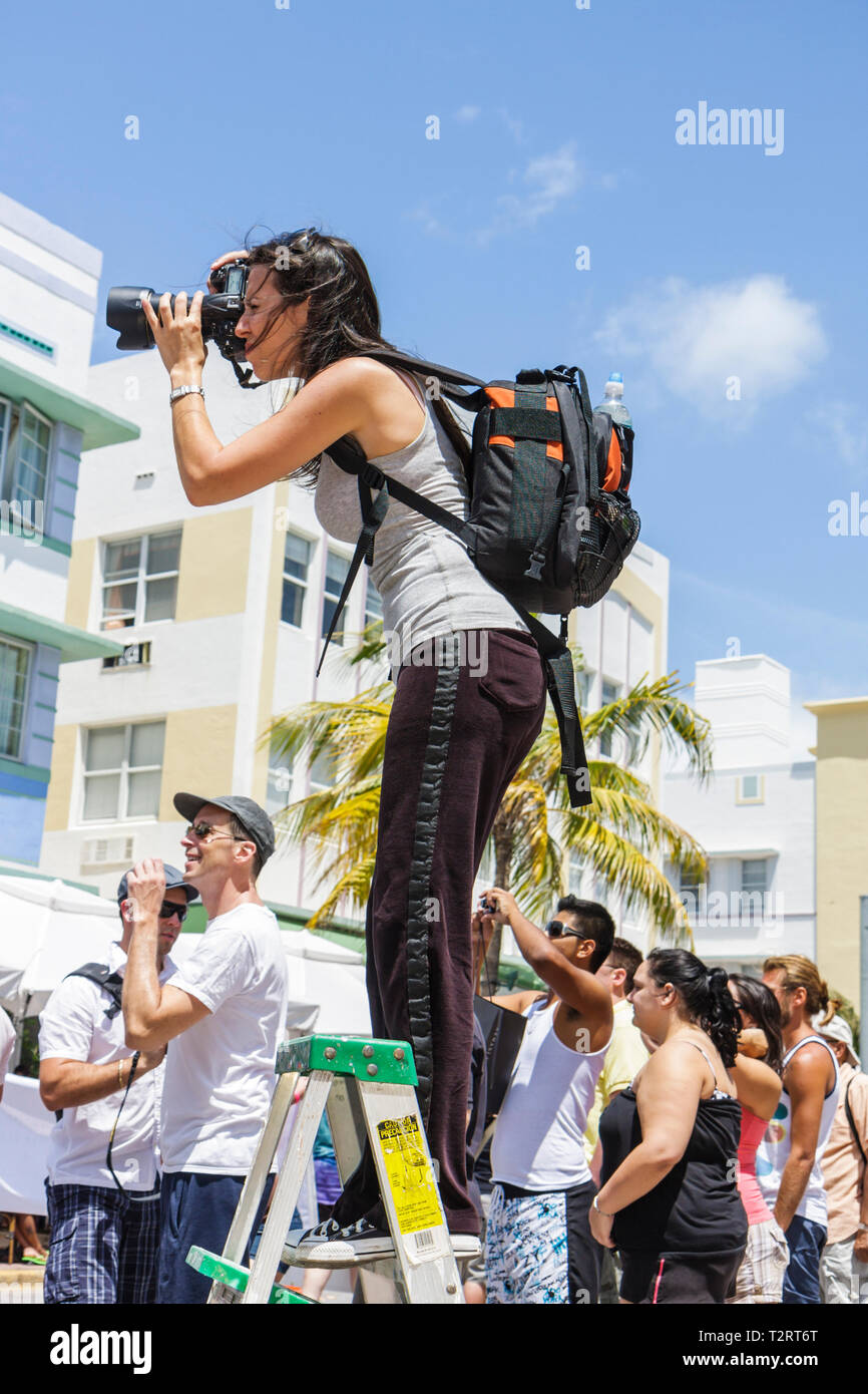 Miami Beach Florida South Beach Ocean Drive Gay Pride Parade festival expo woman photographer ladder camera SLR backpack - Stock Image