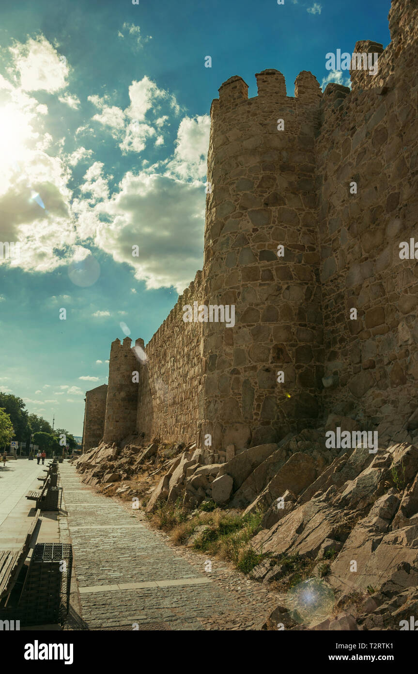Pedestrian promenade beside large city wall with quaint stone tower at Avila. With an imposing wall around the gothic city center in Spain. - Stock Image