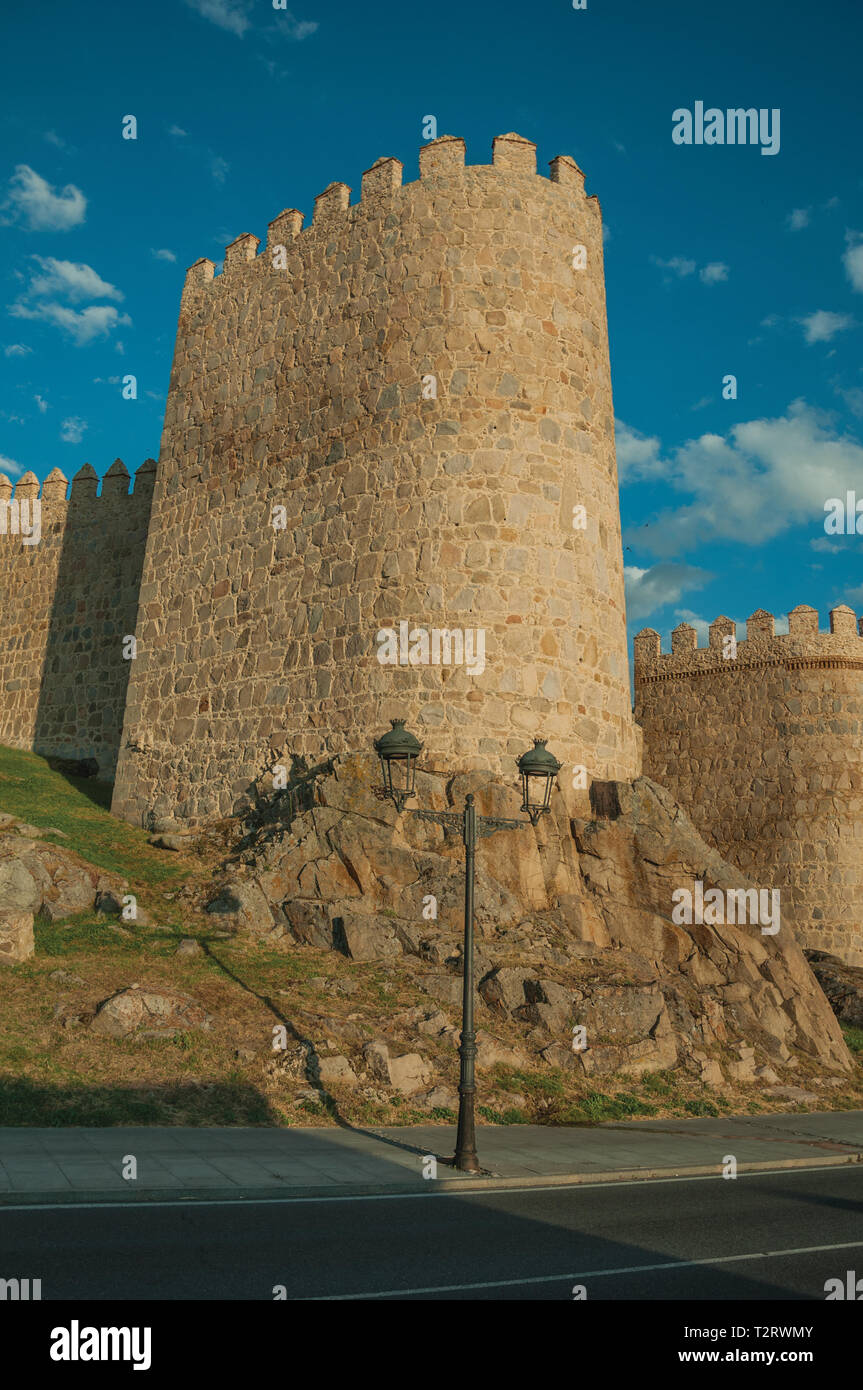 Light post and stone tower over rocky terrain in the large wall of Avila at sunset. With an imposing wall around the gothic city center in Spain. - Stock Image