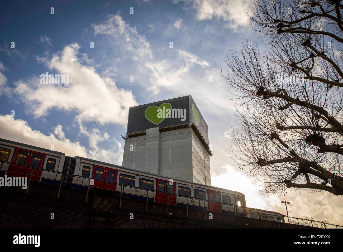 The top of Grenfell Tower pictured with a tube train in the foreground in December 2018. - Stock Image