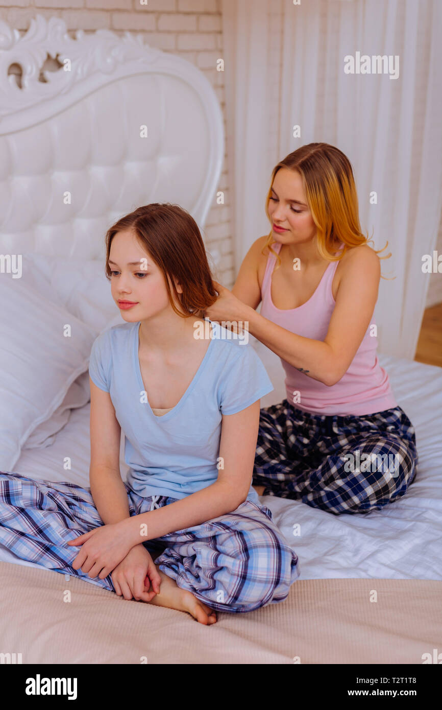 Tying hair. Caring older sister tying hair of her cute teenage sister into braids while sitting on bed - Stock Image