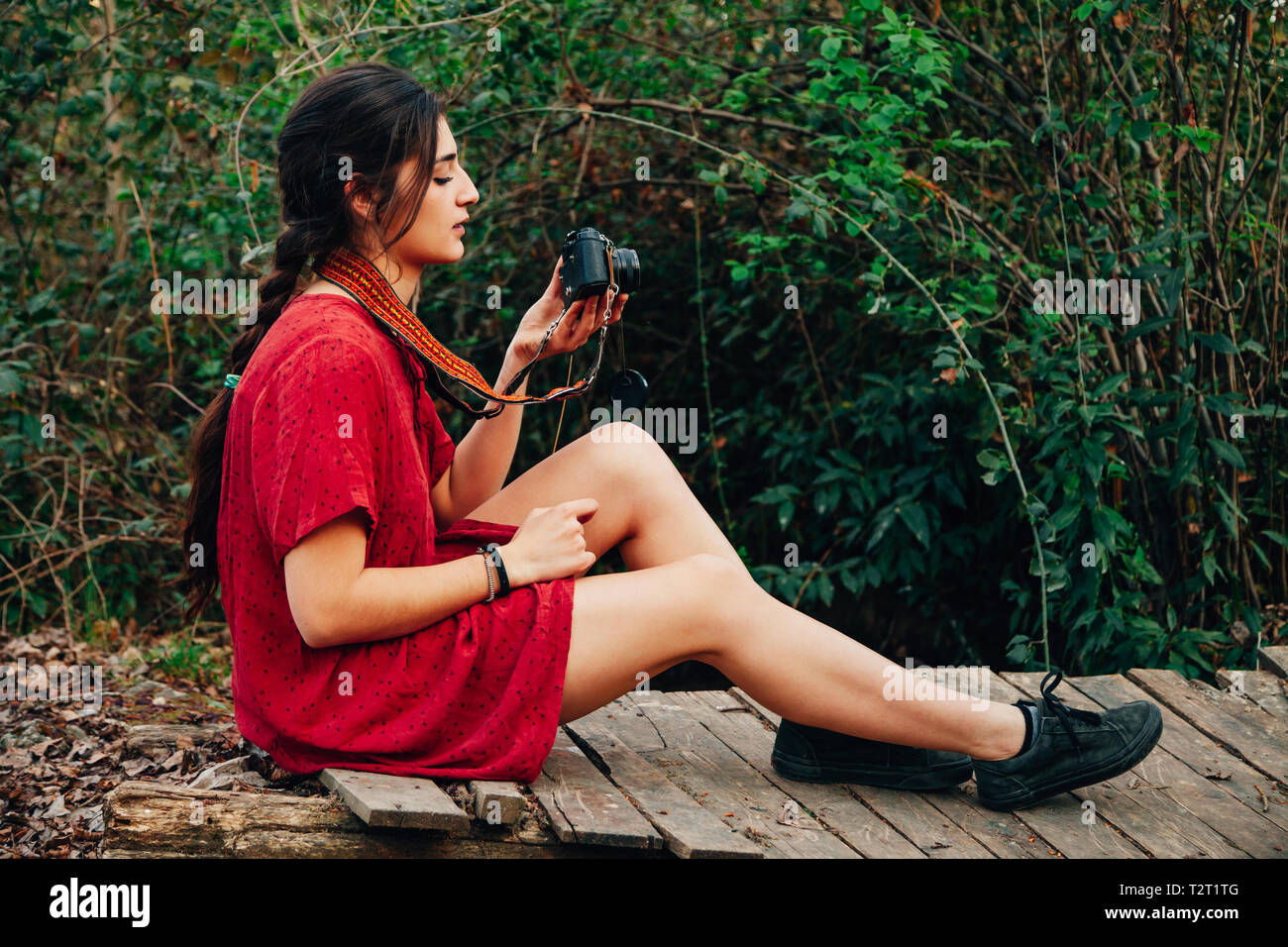 Young woman taking photos in the forest with her analogical camera wearing a red mini dress. - Stock Image