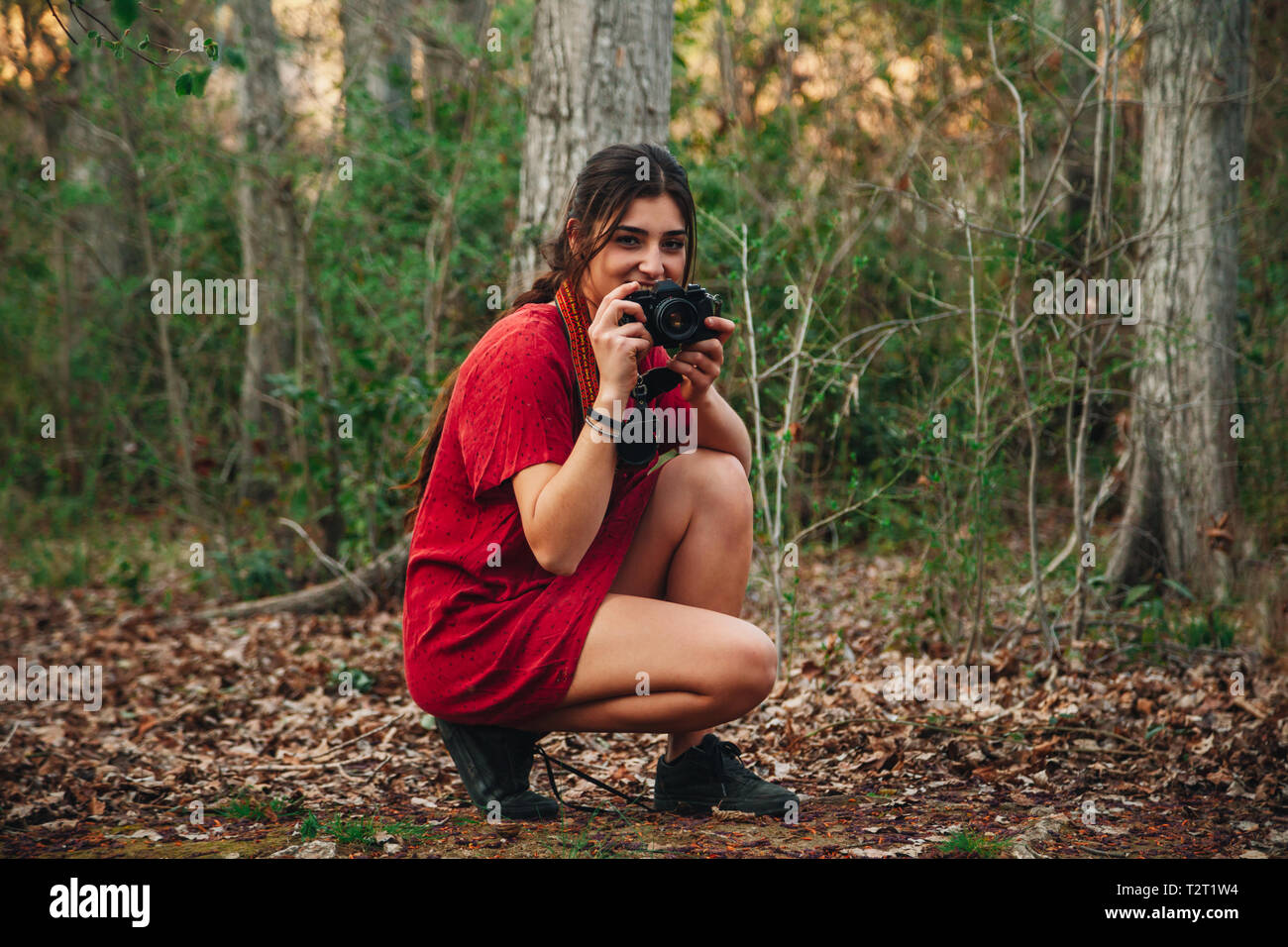 Young smiling woman taking photos in the forest with her analogical camera wearing a red mini dress. - Stock Image