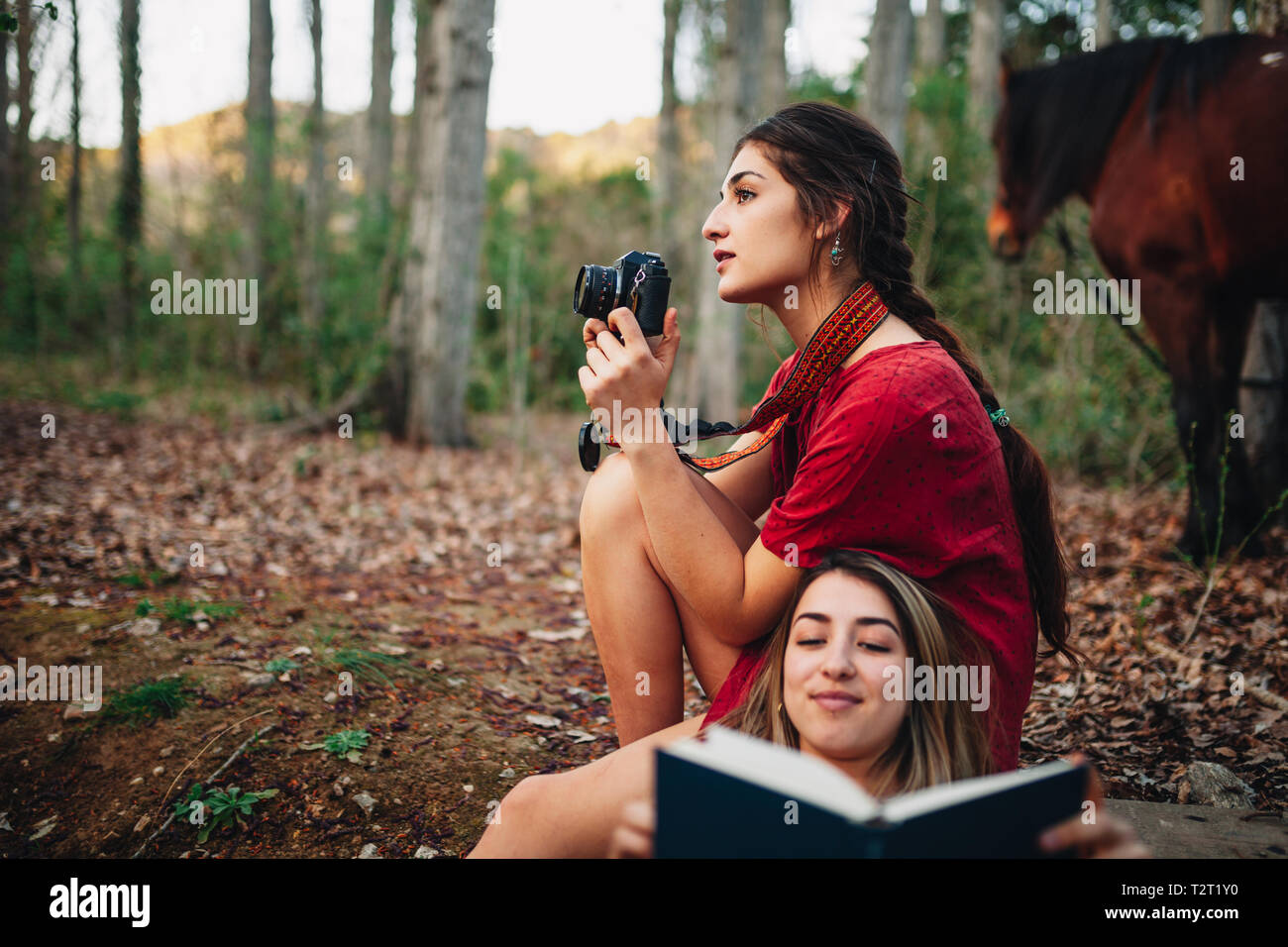 Young smiling couple of women wearing dresses reading a book and taking photos with old camera in the forest with their horse. - Stock Image