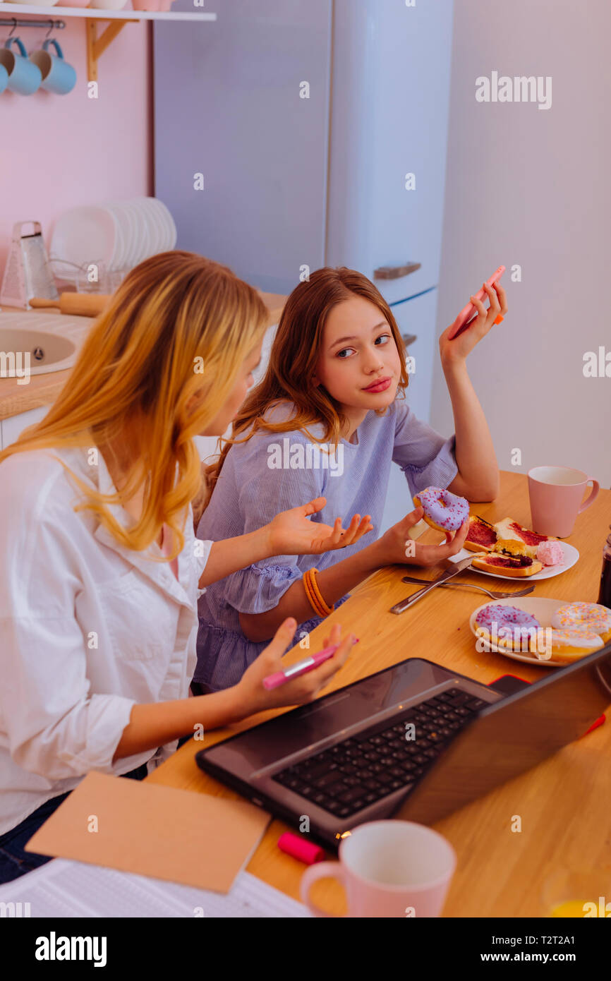 Feeling ashamed. Teenage sister feeling ashamed not paying attention to her sister doing serious project - Stock Image