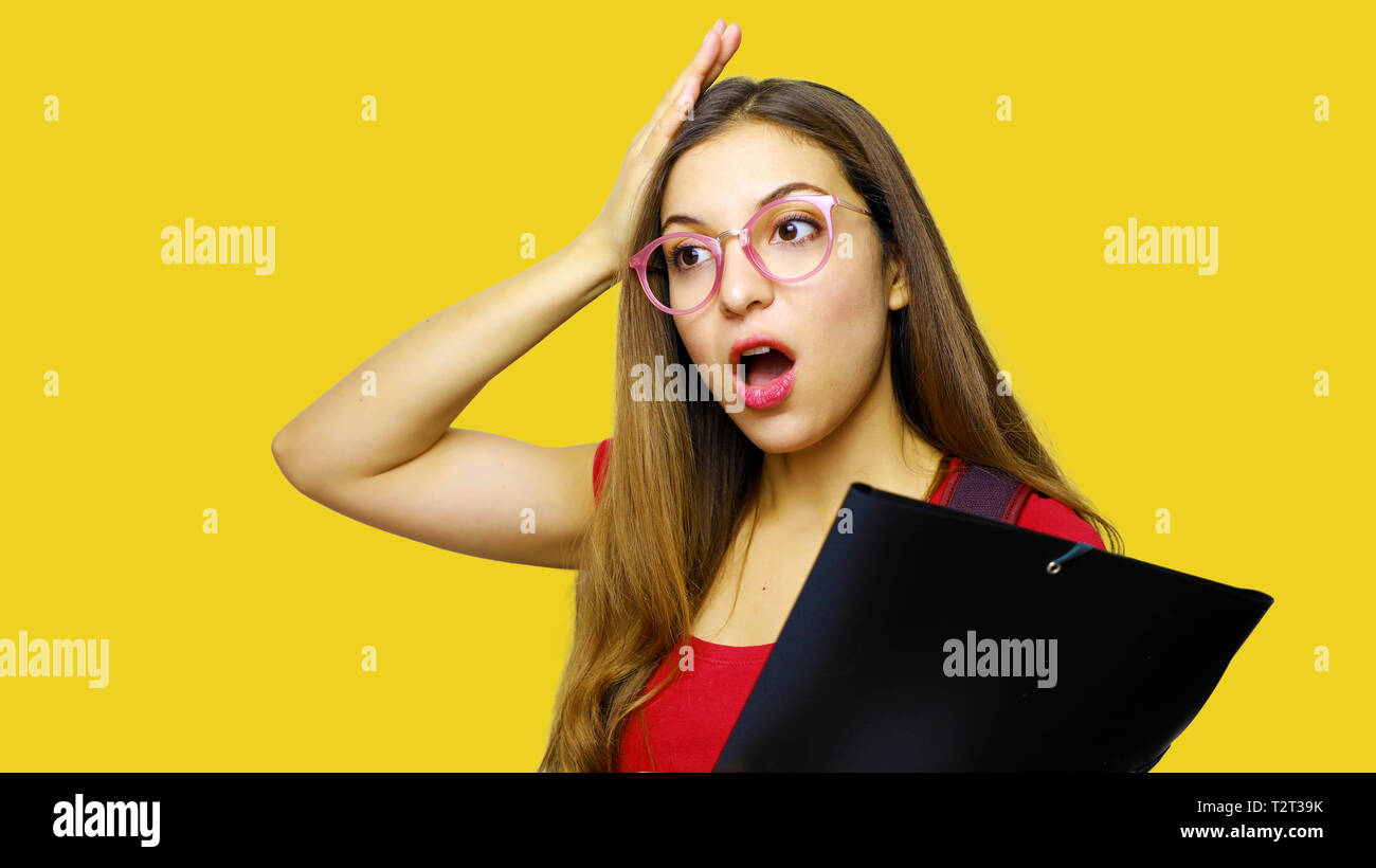 Scared young woman with open mouth holding head with hand and wears spectacles and red t shirt carries folder, forgets to do something important - Stock Image