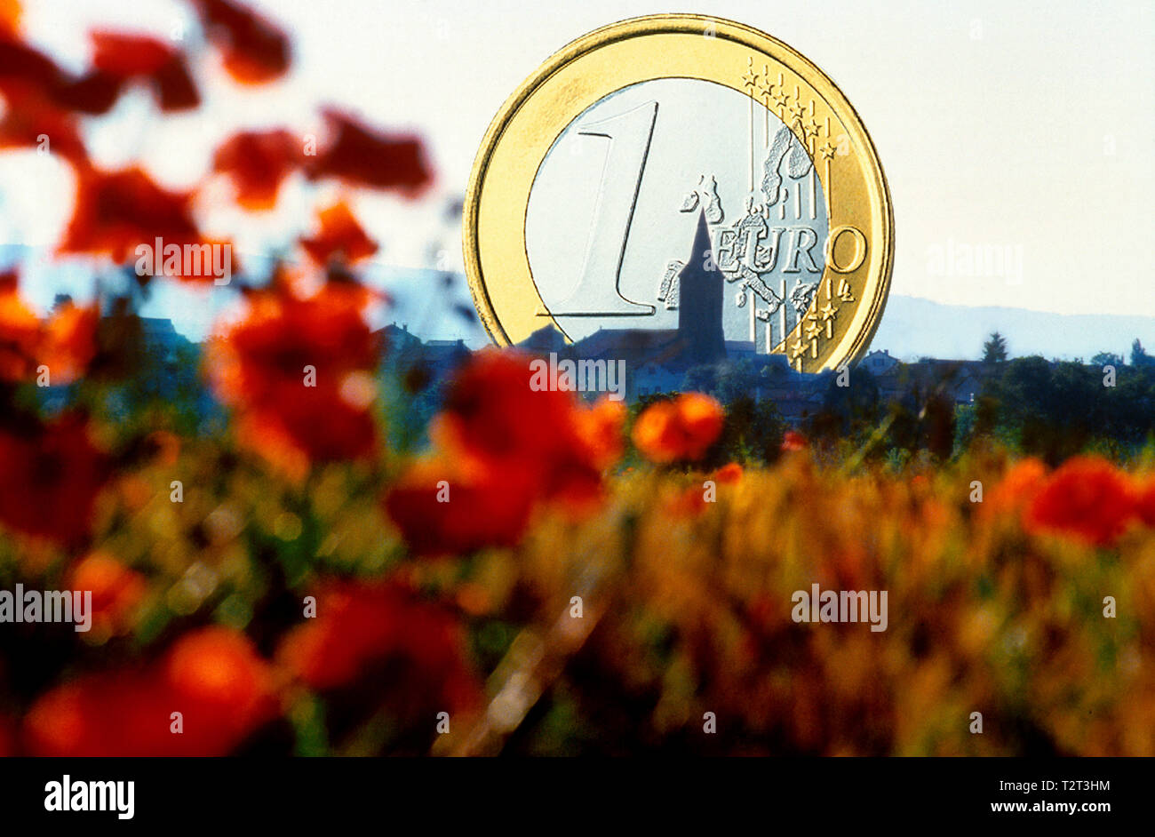 1 euro coin behind a rural landscape with a village (concept) - Stock Image