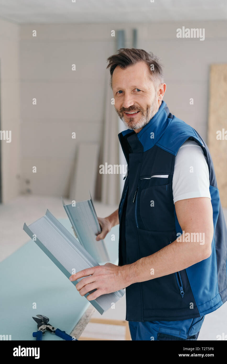 Smiling handyman holding two sections of aluminium as he stands at his work table in a new build house - Stock Image