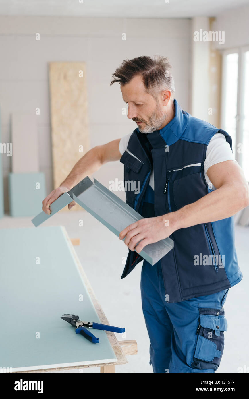 Handyman or builder checking the fit of two aluminium sections with his tin snips lying on the work table below during construction or renovations in  - Stock Image