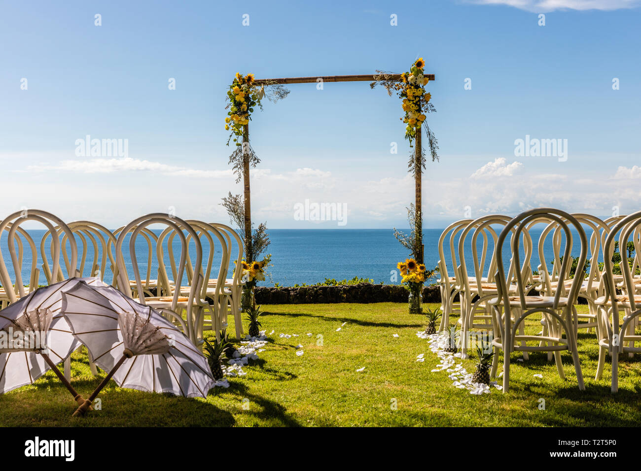 Wedding arch for a ceremony decorated with tropical flowers, and white chairs on the cliff edge of the ocean. Stock Photo