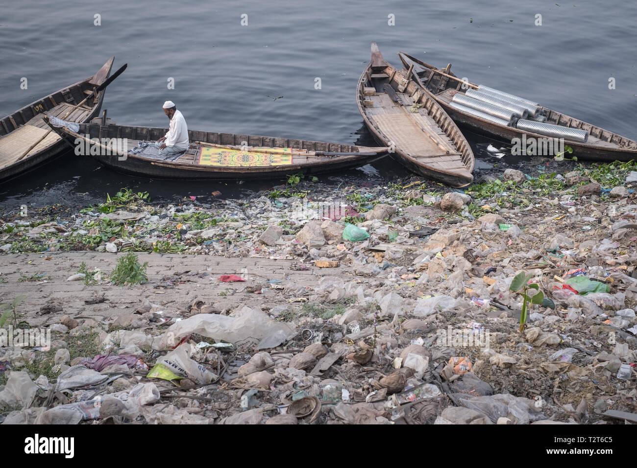 1 muslim man praying on the boat at polluted bank of Buriganga river, Zinzira district, Keraniganj, Dhaka, Bangladesh. - Stock Image