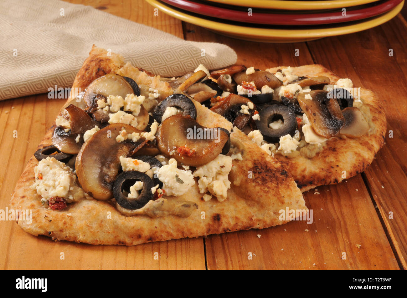 Naan bread topped with black olives, sauteed mushrooms, feta cheese and hummus - Stock Image