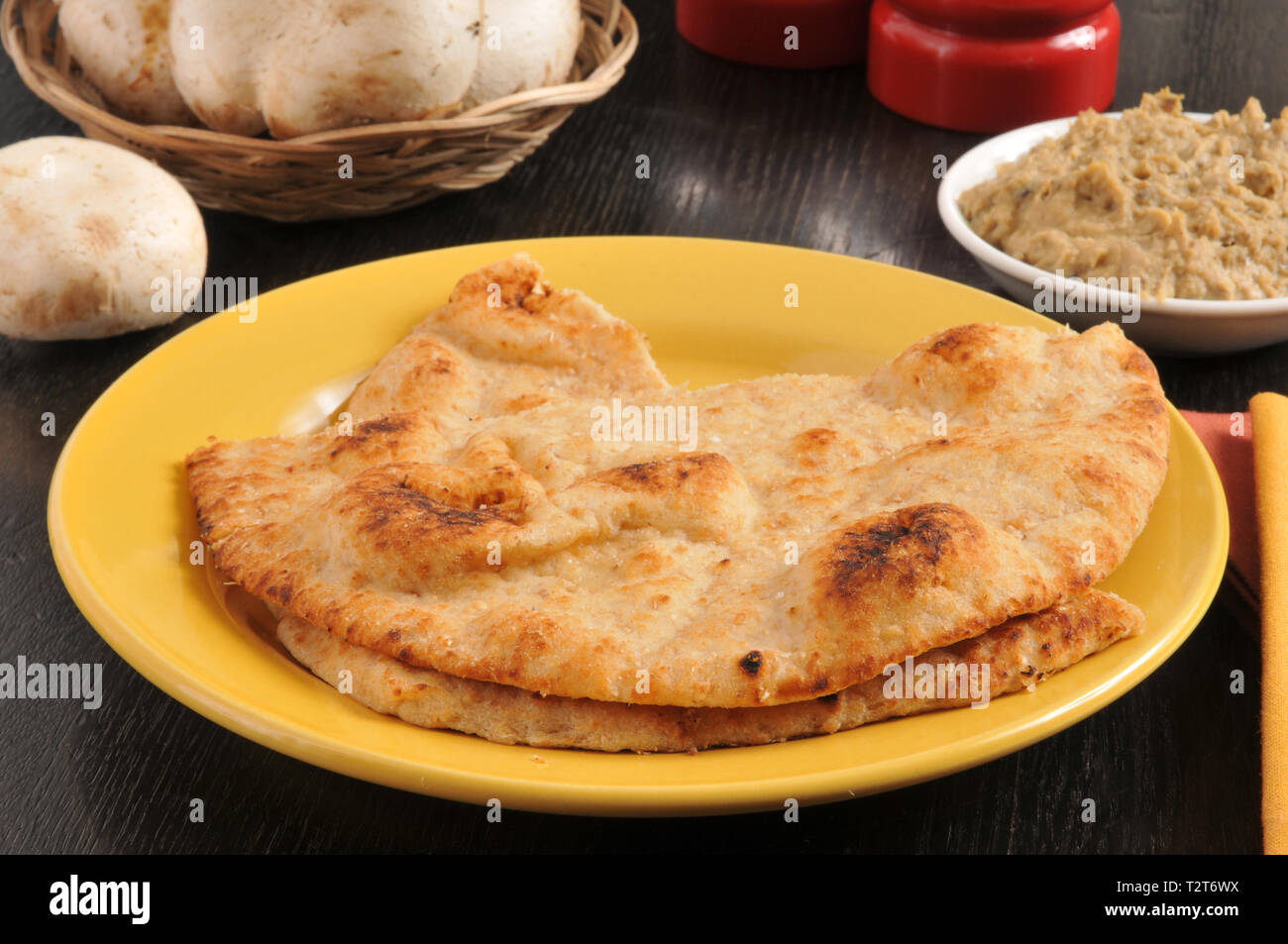 Tandoor baked naan bread on a plate with a bowl of hummus - Stock Image