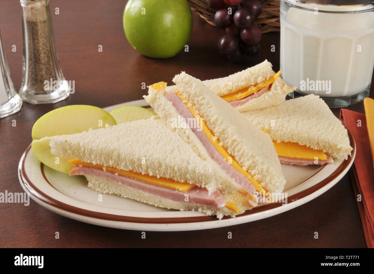A bologna and cheese sandwich with a green apple and milk - Stock Image