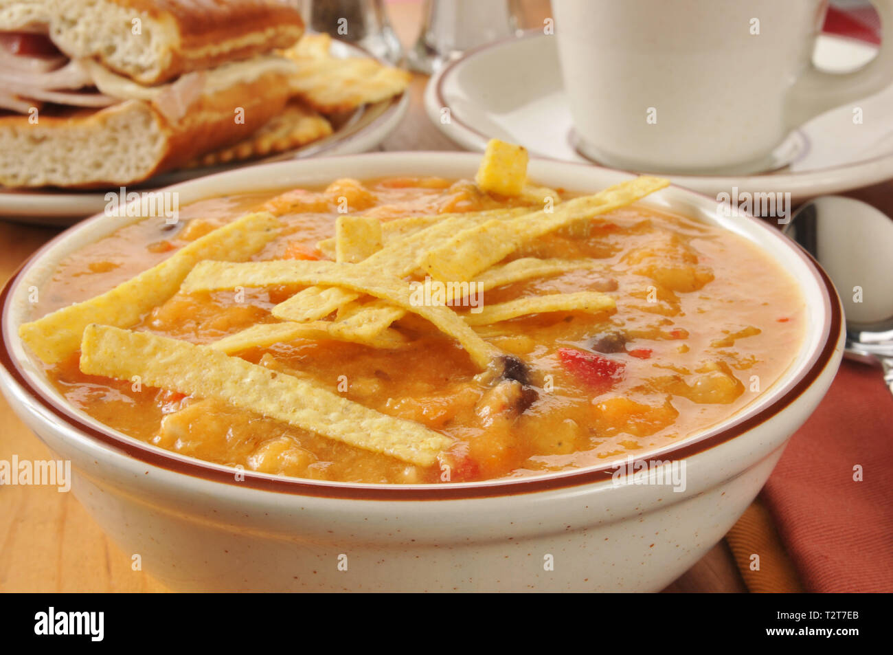 Closeup of a bowl of chicken tortilla soup and a sandwich - Stock Image