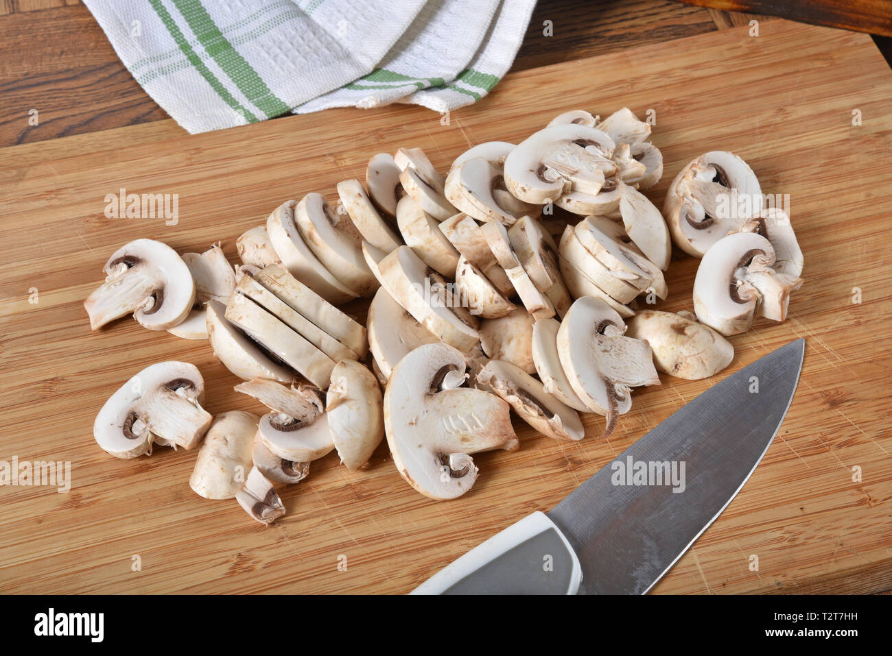 A mound of sliced button mushrooms on a chtting board - Stock Image