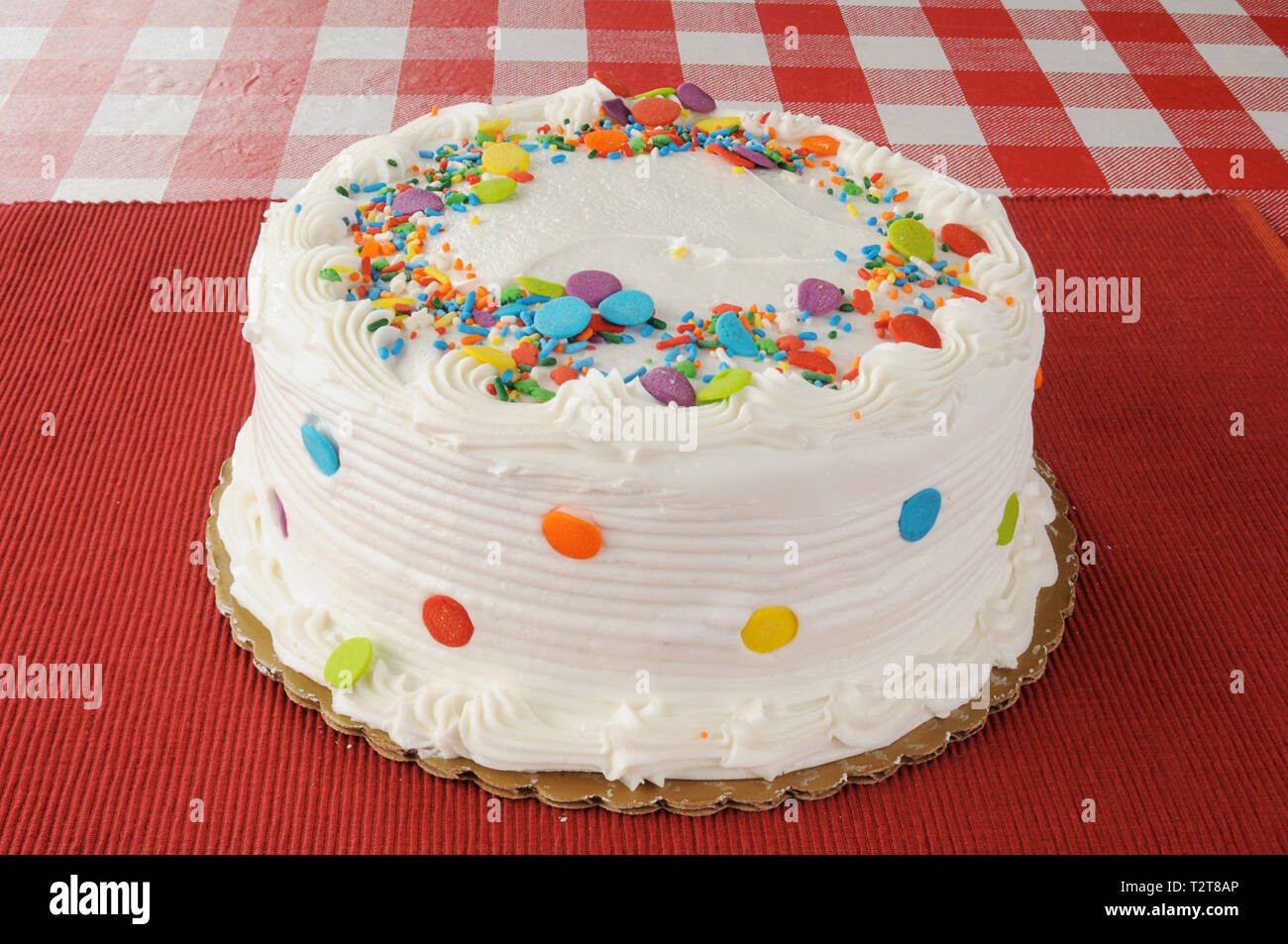 A whole white cake on a checkered tablecloth with candy sprinkles - Stock Image
