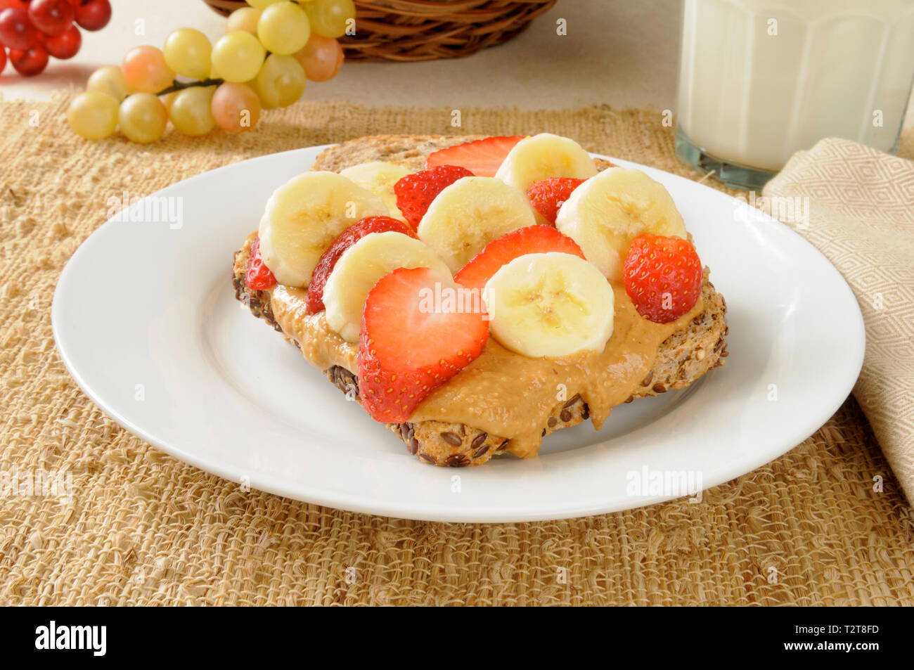 Sprouted seed bread topped with organic peanut butter, bananas and strawberries - Stock Image