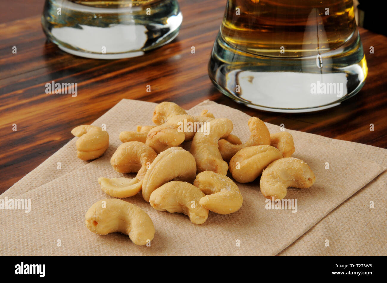 Salted cashews on a cocktail napkin with beer in the background - Stock Image