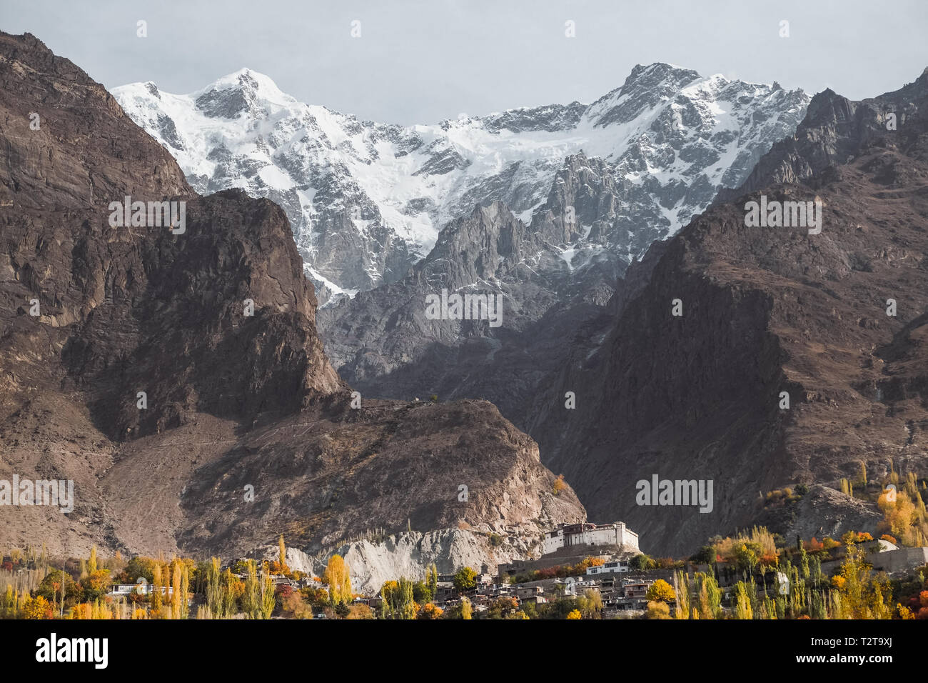 Landscape view of snow capped Ultar Sar mountain in Karakoram range with foliage in autumn in Karimabad. Hunza valley, Gilgit Baltistan, Pakistan. Stock Photo