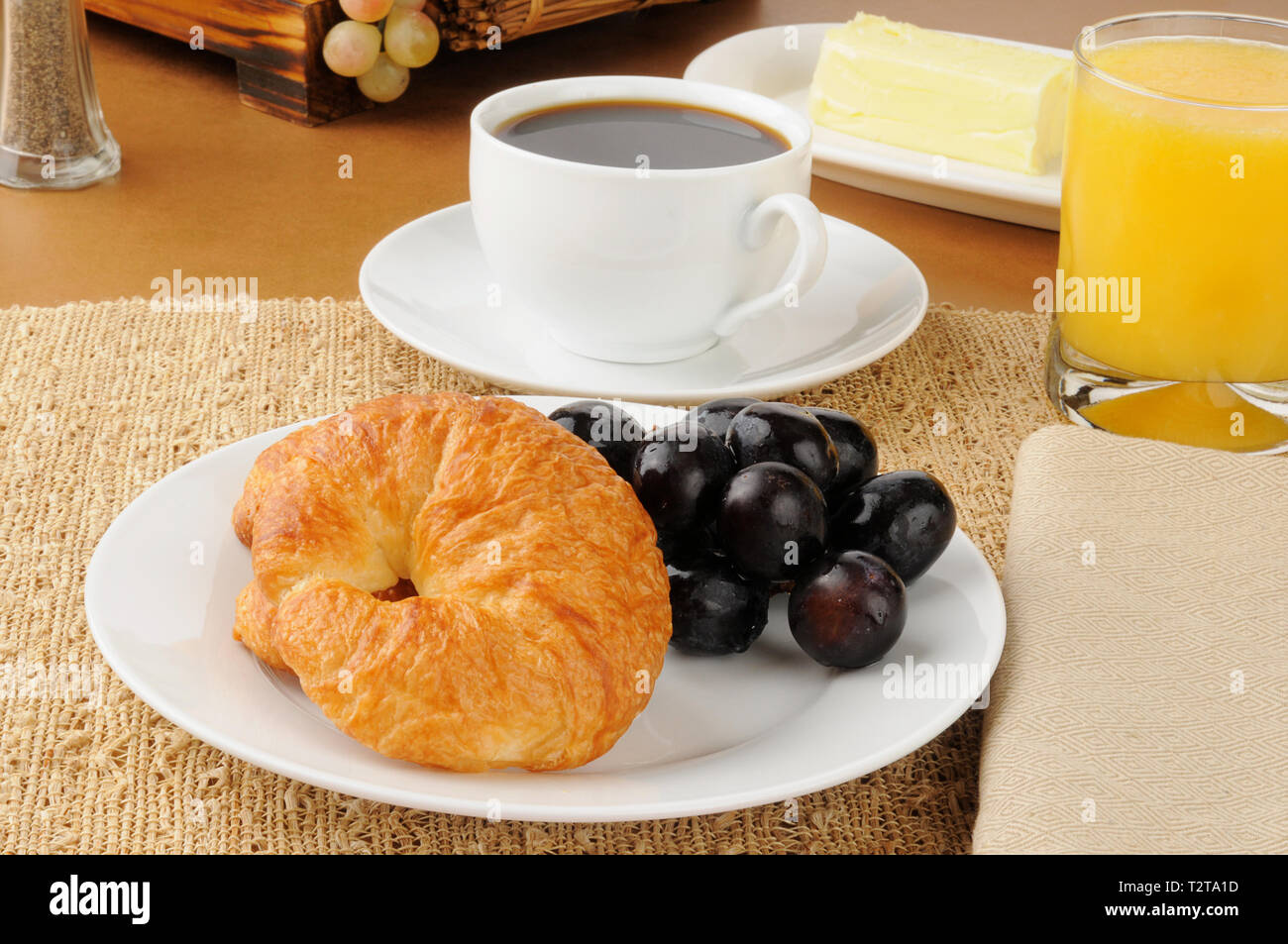A croissant with grapes and coffee - Stock Image