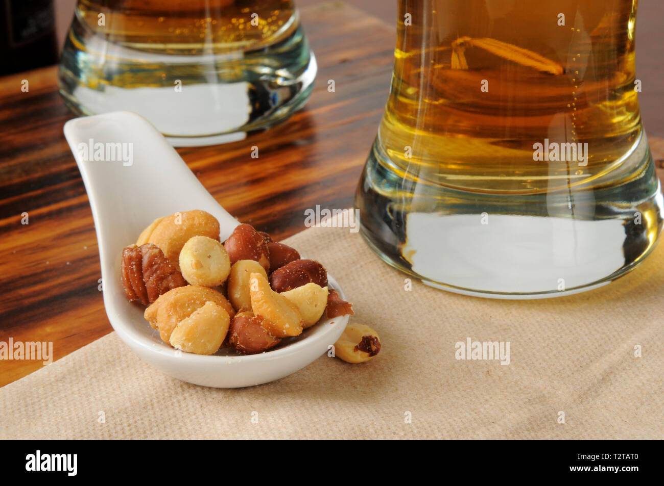 A sample spoon of mixed nuts bar snacks with tall glasses of beer in the background - Stock Image