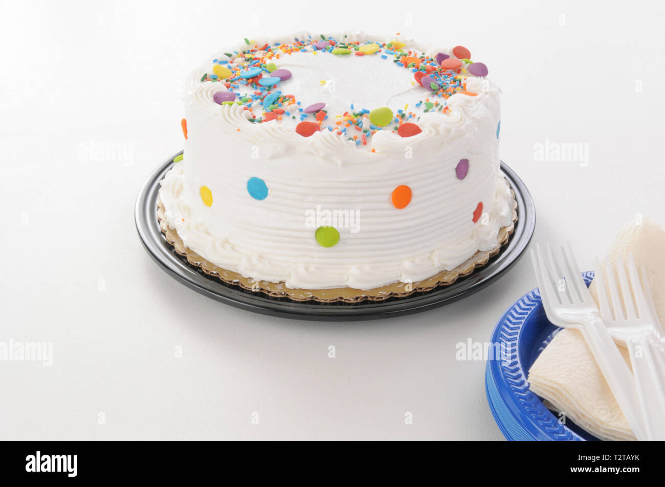 A white cake with candy sprinkles and plastic plates - Stock Image