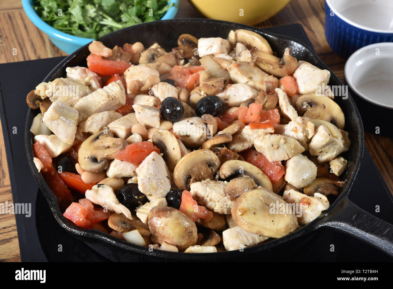 Chicken, tomatoes, mushrooms, onions, black olives and seasonings simmering in a cast iron skillet - Stock Image