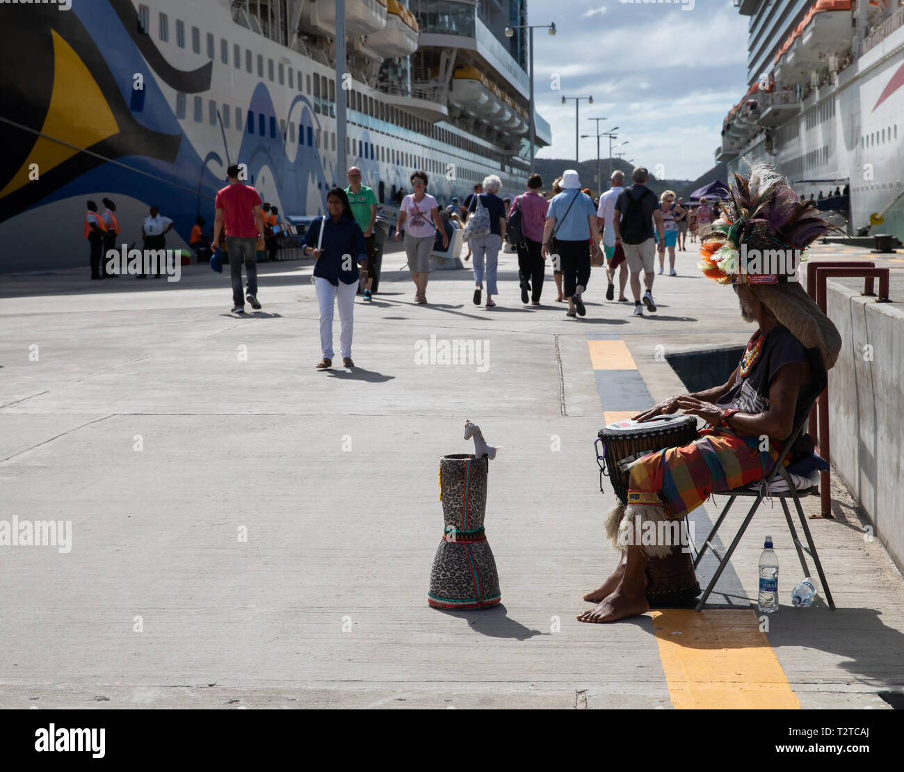 A man plays a drum as people arrive on a cruise ship in Saint John's, Capital of Antigua and Barbuda Stock Photo